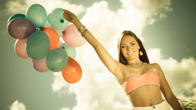 Girl holding balloons sky background Stock Photos