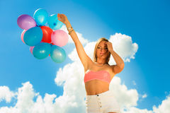 Girl holding balloons sky background Stock Photography