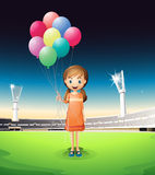 A girl holding balloons standing in the middle of the court Royalty Free Stock Photos