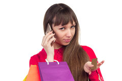 Girl holding banking credit card, colourful shopping paper bags,. Young woman with banking credit card, colourful shopping paper bags and packages, smartphone Royalty Free Stock Photo