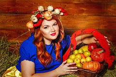 Girl is holding basket with crop of vegetables and fruit. Royalty Free Stock Photo