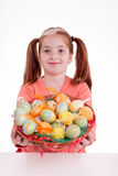 Girl holding a basket of Easter eggs Stock Images