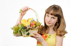 Girl holding basket with fruits and flowers Stock Images