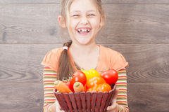 Girl holding a basket of juicy vegetables Stock Photos