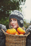 Girl holding basket of pumpkins Stock Image