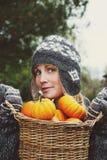 Girl holding basket of pumpkins stock image