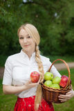 Girl holding basket with red and green apples in the park Stock Image