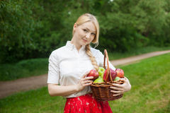 Girl holding basket with red and green apples in the park Royalty Free Stock Photography
