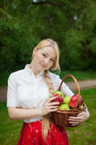 Girl holding basket with red and green apples in the park Royalty Free Stock Photo