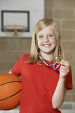 Girl Holding Basketball And Medal In School Gymnasium Royalty Free Stock Photo