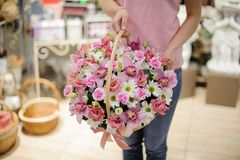 Girl holding a beautiful basket of pink orchids and white camomiles Stock Photo