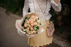 Girl holding a beautiful bouquet of champagne color roses. Girl in the white shirt and beige skirt holding in her hands a beautiful bouquet of champagne color stock image