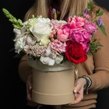 A girl is holding a beautiful bouquet of exclusive fresh flowers in a box. A great gift for women`s day stock photos