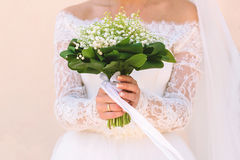 Girl holding a beautiful bouquet of flowers near a wall Stock Image