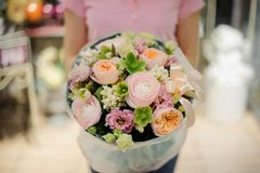 Girl holding a beautiful bouquet of green and rose colour tender flowers Royalty Free Stock Photos