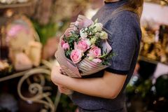 Girl holding a beautiful bouquet of pink and white roses. Decorating with a green leaves Royalty Free Stock Photography