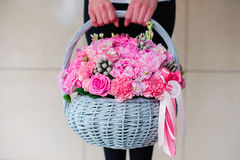 Girl holding beautiful pink bouquet of mixed flowers in basket Royalty Free Stock Photography