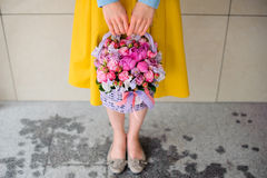 Girl holding beautiful pink bouquet of mixed flowers in basket. No face Royalty Free Stock Images