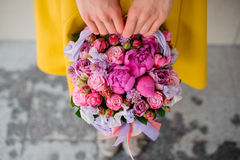Girl holding beautiful pink bouquet of mixed flowers in basket Royalty Free Stock Images