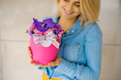 Girl holding beautiful pink bouquet of mixed flowers in vase Stock Photo