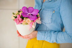 Girl holding beautiful pink bouquet of mixed flowers in vase Royalty Free Stock Images