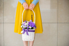 Girl holding beautiful purple bouquet of mixed flowers in basket Royalty Free Stock Photography