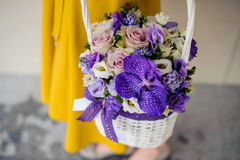 Girl holding beautiful purple bouquet of mixed flowers in basket Royalty Free Stock Photo