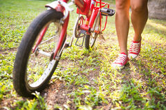 Girl is holding bicycles in park Stock Images
