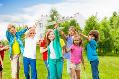 Girl holding big airplane toy and children behind. Girl holding big white airplane toy and children behind catching her in the field during summer day Royalty Free Stock Images