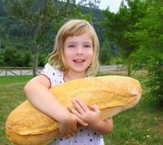 Girl holding big bread humor size hungry child stock images