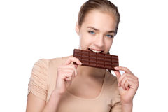Girl holding big chocolate bar in her tooths Stock Photography