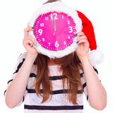 Girl holding big clock in Christmas hat on his face Stock Photo