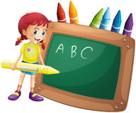 A girl holding a big crayon standing in front of a blackboard Royalty Free Stock Photography