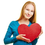 Girl holding big red heart. Blonde girl holding big red heart in front of her chest Royalty Free Stock Images