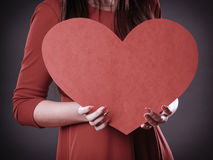Girl holding big red heart in hands Stock Photography