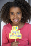 Girl (7-9) holding birthday card, smiling, front view, close-up, portrait Stock Photo