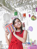 Girl Holding Birthday Present At Party Stock Images