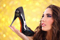 Girl holding a black high heel shoe Royalty Free Stock Photos