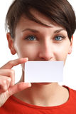Girl holding blank business card. Beautiful girl holding an empty business card, hiding her mouth Royalty Free Stock Images