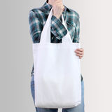 Girl is holding blank cotton tote bag, design mockup. Royalty Free Stock Images