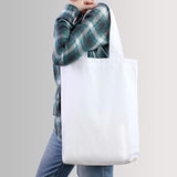 Girl is holding blank cotton tote bag, design mockup. Girl is holding white blank cotton tote bag, design mockup. Handmade shopping bag for girls royalty free stock photo