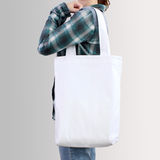 Girl is holding blank cotton tote bag, design mockup. Royalty Free Stock Image