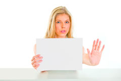 Girl holding blank paper and showing stop gesture Stock Image