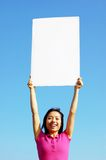 Girl Holding Blank Sign. In front of big blue sky royalty free stock photos