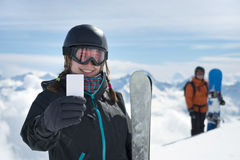 Girl holding blank ski ticket smiling Stock Photo