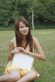 Girl holding blank white board on grass royalty free stock photo