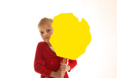Girl holding blank yellow sign. A studio view of a young girl holding an irregular shaped,  blank yellow sign Royalty Free Stock Images