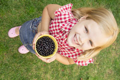 Girl holding blueberries in a bucket Royalty Free Stock Image