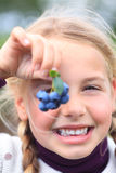 Girl holding blueberries in front of her eye royalty free stock photo