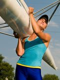Girl holding boat. Rower girl carrying sport boat outdoors summer Royalty Free Stock Photography